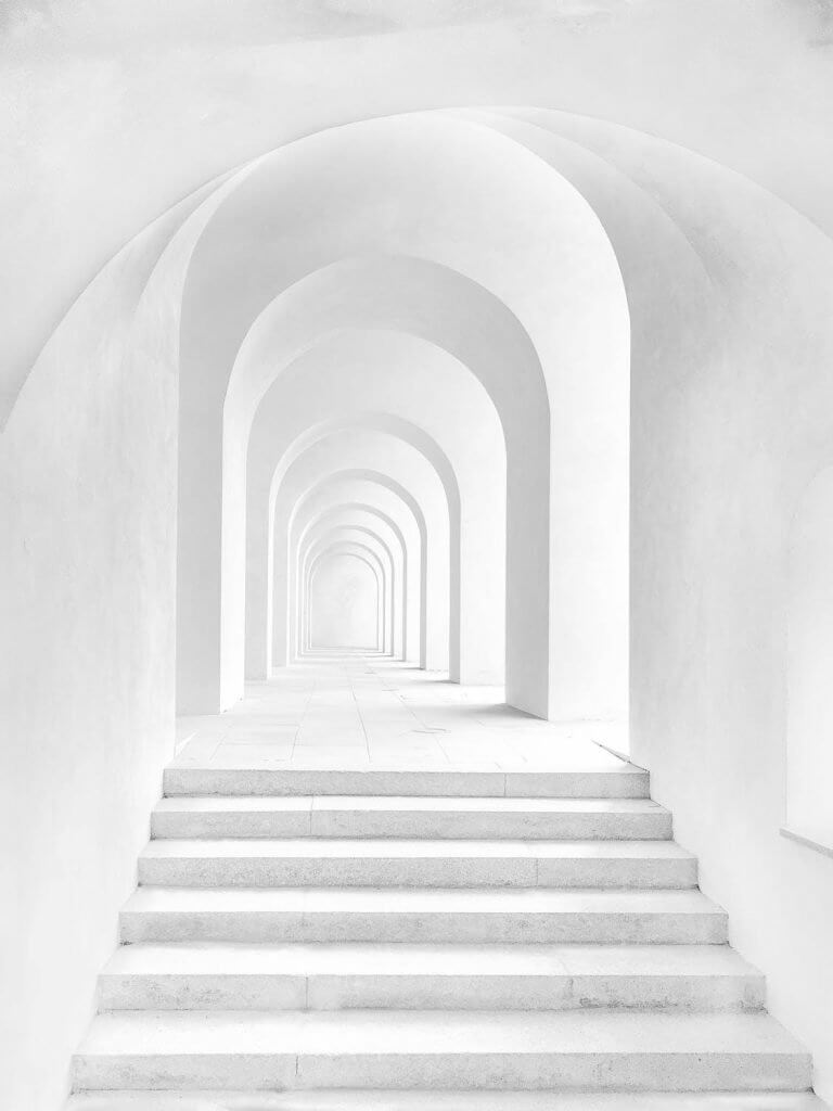 Steps leading to a white hallway with successive arches in a building's interior.