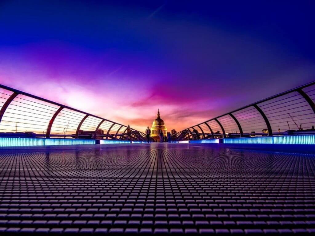 A purple footbridge under an evening sky, leading to a capitol building in the distance.