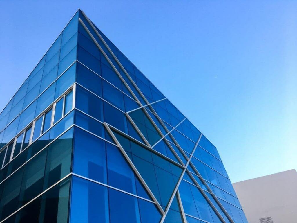 A low angle of a blue cubical building featuring a glass design and modern, symmetrical external frames.